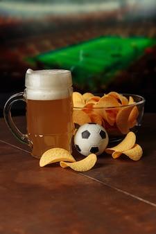 サッカーゲームの垂直方向の画像と画面の前にビールサッカーボールとスナックのガラス