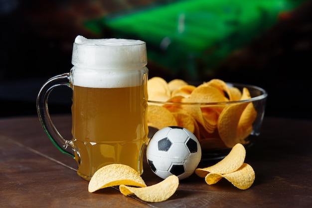 Стакан пива, футбольный мяч и закуска на футбольном матче.