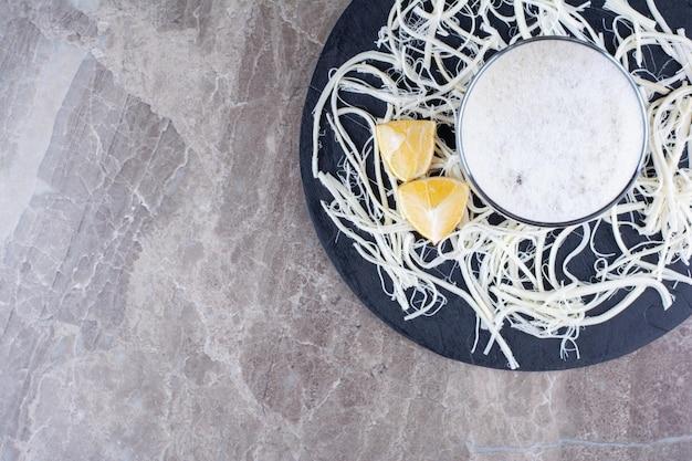 Стакан пива с сыром и лимонами на темной доске. фото высокого качества