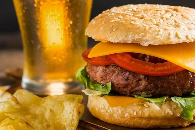 チーズバーガーとチップスとビールのグラス
