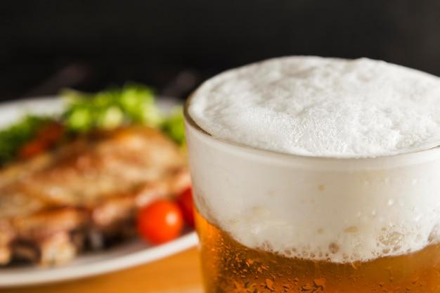 焦点がぼけたステーキとビールのグラス