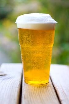 自然の空間に木製のテーブルの上の泡とビールのグラス
