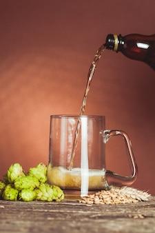 Стакан пива с хмелем и ячменем на деревянном столе