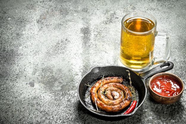 Стакан пива с горячей колбасой. на деревенском фоне.