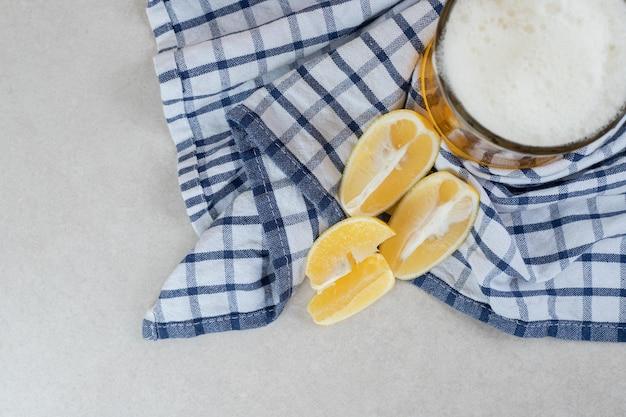 식탁보에 레몬 조각과 맥주 한 잔