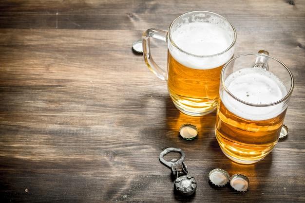 Стакан пива с пробками и открывалкой для бутылок. на деревянном столе.