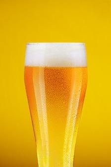 黄色の背景に水滴とビールのガラス