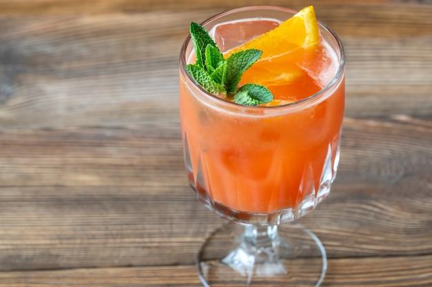 오렌지 슬라이스와 신선한 민트로 장식 된 벨몬트 브리즈 칵테일 잔