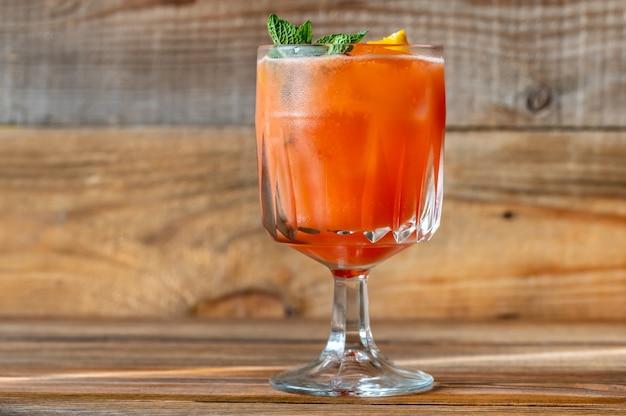 オレンジスライスとフレッシュミントを添えたベルモントブリーズカクテルのグラス