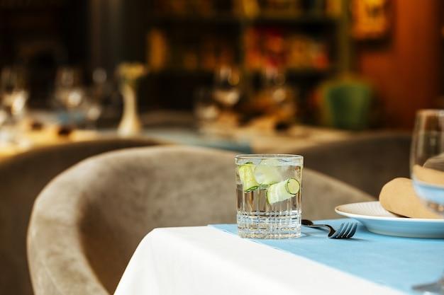 レストランのテーブルに氷とキュウリと飲み物のガラス