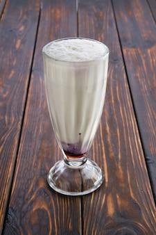 Стакан молочного коктейля из черной смородины на деревянном столе