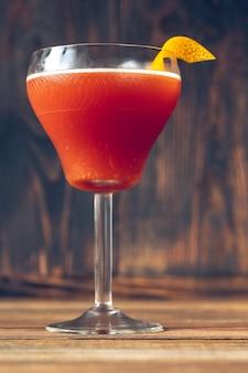 오렌지 껍질로 장식 된 마티니 잔에 피와 모래 칵테일 잔