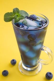 黄色いテーブルの上に氷とブルーベリーと青いカクテルドリンクのグラス。閉じる。