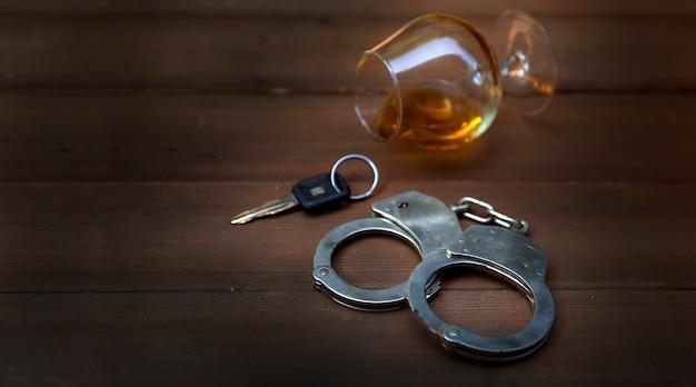 Стакан бренди, ключи от машины и наручники. концепция вождения в нетрезвом виде
