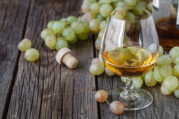 Бокал бренди с кисточкой винограда на столе, праздник урожая