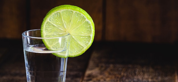 Стакан бразильского дистиллированного напитка с лимоном, который называется кашака или «пинга», копировать пространство