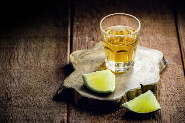 サトウキビから蒸留されたブラジルの飲み物であるカシャーサのグラスに、コピースペース付きのレモン(ピンガとも呼ばれます)を添えて