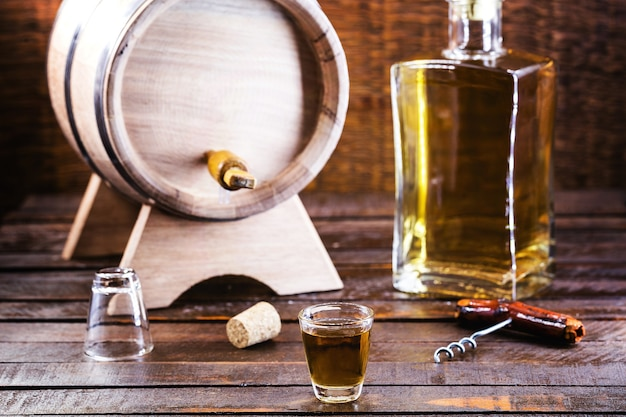 Cachaça의 유리, 브라질에서 증류 된 알코올 음료, 백그라운드에서 병 및 배럴