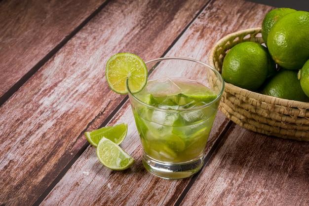 Стакан кайпириньи с лимоном на состаренном деревянном столе, типичный бразильский напиток