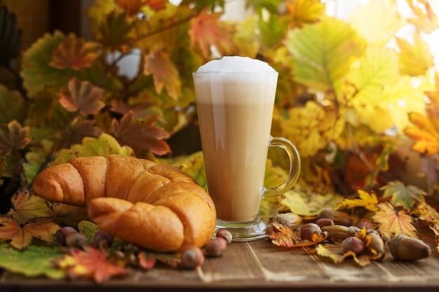Стакан капучино и круассан в желтой осенней листве с желудями и орехами. осенний завтрак.