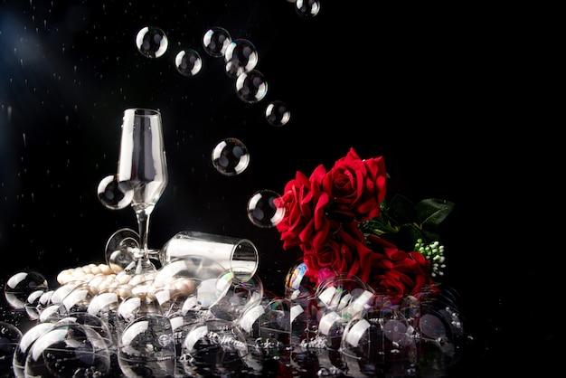 Бокал шампанского, красные розы, жемчужное ожерелье и мыльные пузыри, черный фон, выборочный фокус.