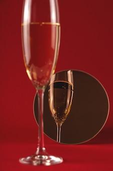 Бокал шампанского с отражением в маленьком круглом зеркале на красном