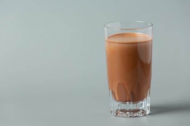 Стакан шоколадного молока на темной поверхности.