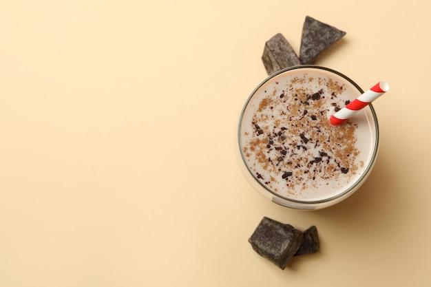 베이지 색 배경에 초콜릿 밀크 쉐이크와 초콜릿 조각의 유리