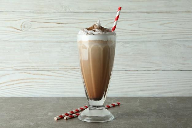 Стакан шоколадного молочного коктейля и соломки на сером столе