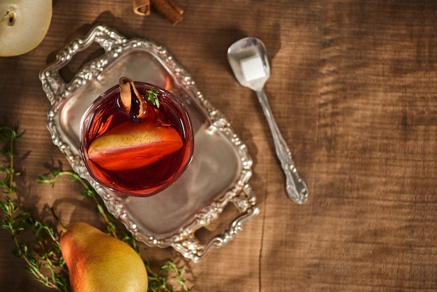 サイダーペアカクテルまたはレモネード、シナモンスティック、木の表面のアニススターのグラス。