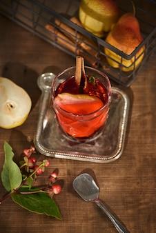 サイダーペアカクテルまたはレモネード、シナモンスティック、木の表面のアニススターのグラス。 Premium写真