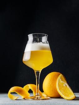 暗い背景に柑橘系ビールのガラス