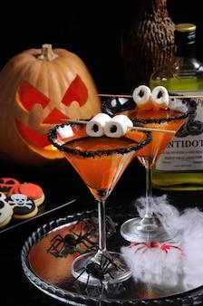 ハロウィーンのテーブルにマシュマロの目で黒砂糖で飾られた柑橘類のマティーニのガラス