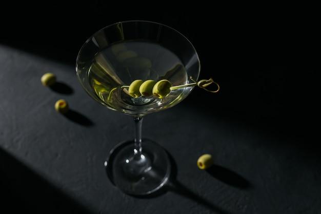 黒の背景に暗い石のテーブルにオリーブと古典的なドライマティーニカクテルのガラス