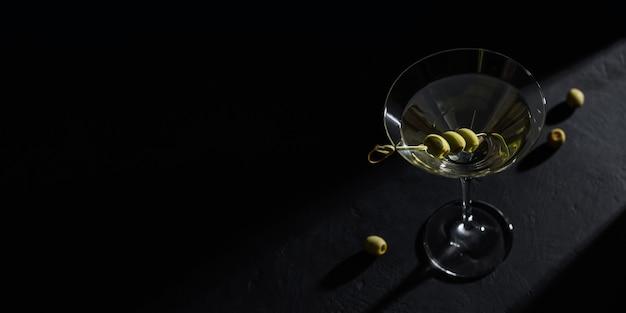 黒の背景に暗い石のテーブルにオリーブとクラシックなドライマティーニカクテルのガラス。あなたのテキストのための空きスペース付き