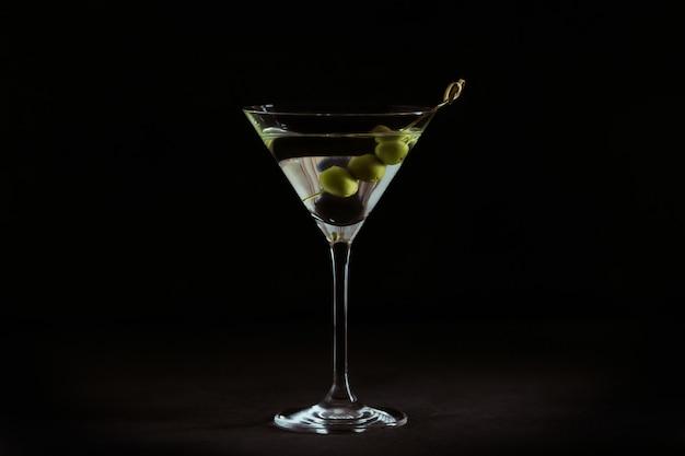 黒に対して暗い石のテーブルにオリーブとクラシックなドライマティーニカクテルのグラス。