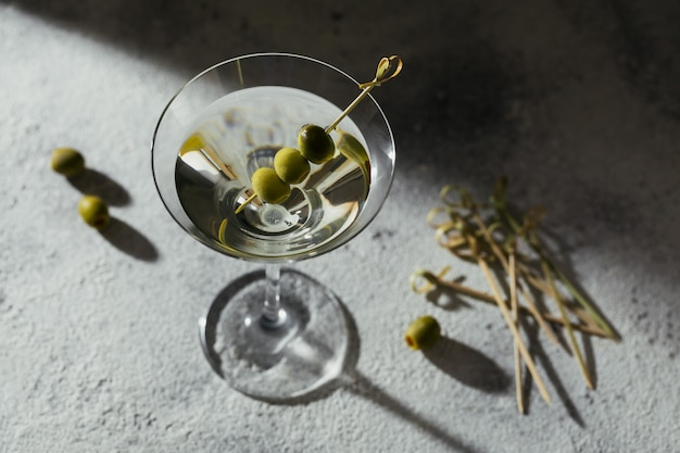 Стакан классического сухого коктейля мартини с оливками на сером каменном фоне. со свободным местом для вашего текста