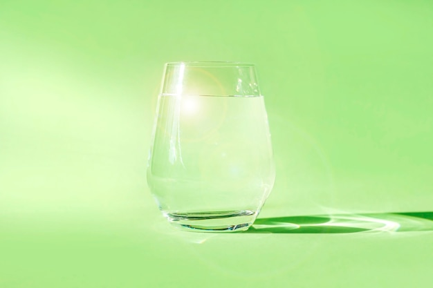 緑の背景にきれいな淡水のガラス。春の生態学的に純粋な水。デトックス、静水のエネルギー