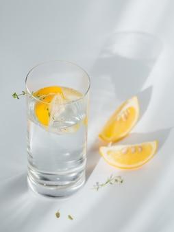 太陽の光が差し込む白い壁に氷とレモンが入ったきれいなミネラルスパークリングウォーターのグラス。ガラスからの強い影とまぶしさのある光。朝食、新鮮な朝の飲み物