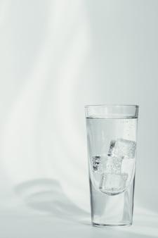 白い背景の上の氷ときれいなミネラルスパークリングウォーターのガラス