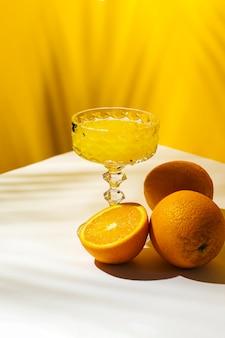 야자수 그늘과 햇빛 아래에서 칵테일 또는 오렌지 주스 한 잔.