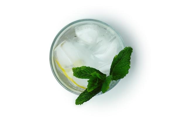 白い表面に分離されたレモンとミントとカクテルのグラス