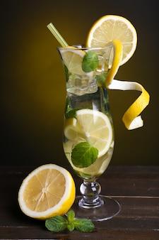 濃い黄色のテーブルにレモンとミントのカクテルのグラス