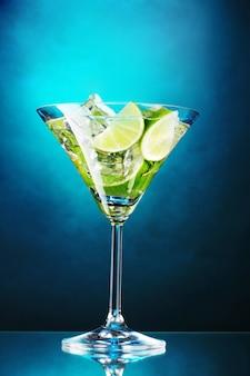 Стакан коктейля с лаймом и мятой на синем фоне