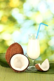 Стакан кокосового молока и кокосов на зеленой поверхности крупным планом