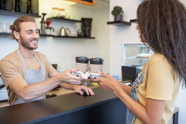 커피 한잔. 카페에서 여자에게 테이크 아웃 커피 잔을주는 바 뒤에 앞치마에 쾌활한 남자