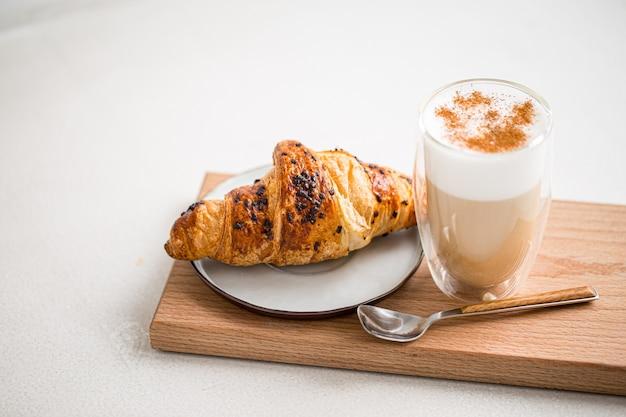 Стакан кофе латте с корицей и круассаном