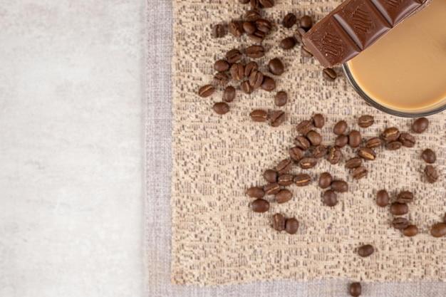 黄麻布にチョコレートとコーヒー豆とコーヒーのグラス。