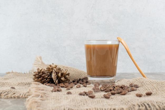 コーヒー豆と黄麻布のスプーンとコーヒーのグラス。