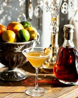 Стакан коньяка и ваза с фруктами на столе